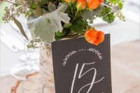 a bold rustic centerpiece of a wood slice, a candle, a chalkboard table number and a bright floral arrangement