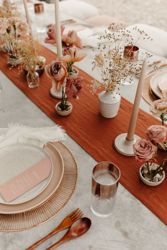 a bold wedding tablescape with a rust-colored table runner, neutral candles, pink blooms, blush menus and wooden cutlery