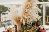 a bright fall centerpiece of bold blooms, greenery, pampas grass and a gold table number in front of wheat