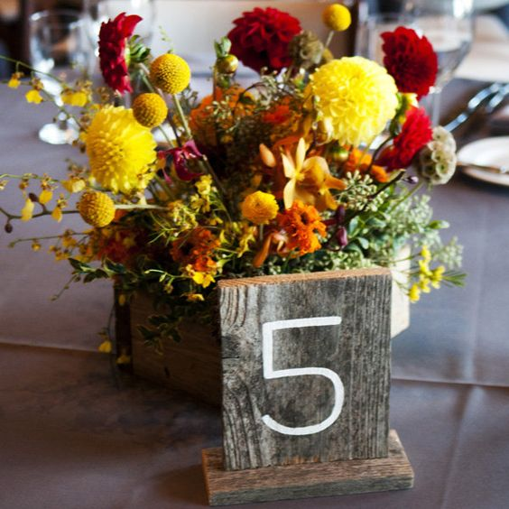 a bright fall floral centerpiece with greenery and a wooden table number for styling your tablescape
