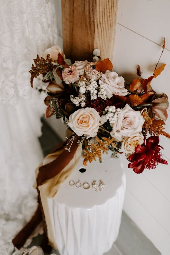 a bright fall wedding bouquet of blush, deep red and rust blooms, colorful fall foliage and bold ribbons is a very cool and chic idea for a boho wedding
