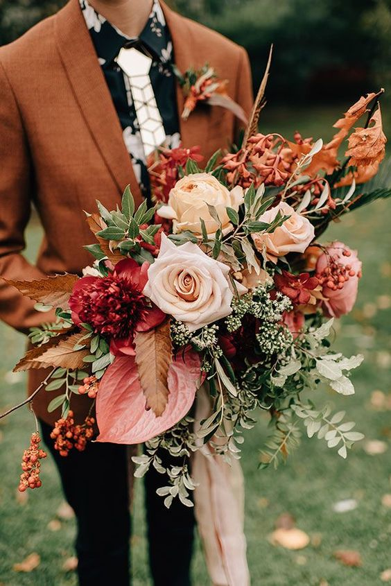 a bright fall wedding bouquet of blush, neutral, deep red and pink blooms, greenery, berries and twigs with long ribbons is amazing