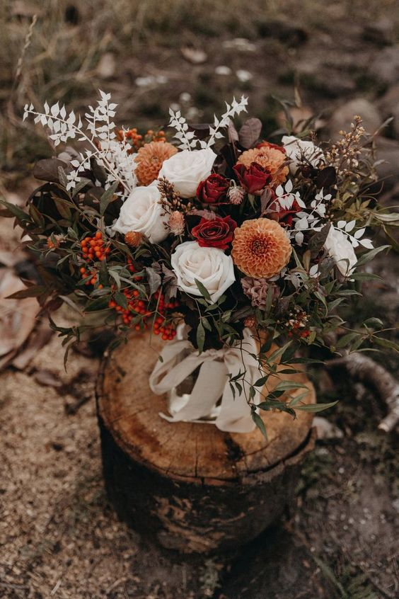 a bright fall wedding bouquet of white, orange, rust, deep red blooms, berries and lots of various foliage and leaves is wow