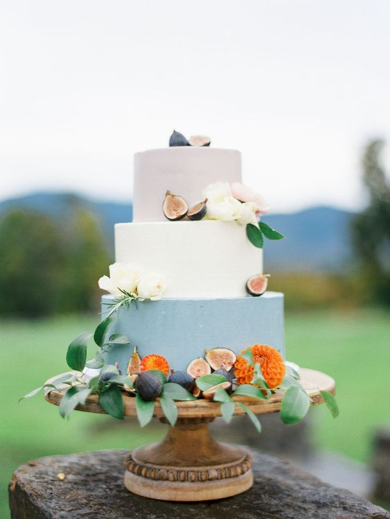 a bright fall wedding cake with a blush, white and blue tier, blooms and figs is a laconic and chic idea