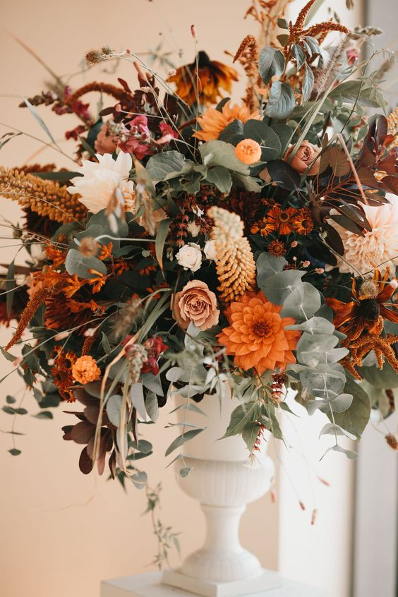 a bright fall wedding centerpiece with a white vintage urn, greenery, lots of blooms in orange, blush, rust and coffee shades