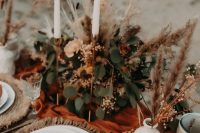 a bright fall wedding table setting with woven placemats, white porcelain, orange napkins and a table runner, greenery, pampas grass and tall and elegant candles