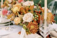 a bright fall wedding tablescape with a bold floral centerpiece with berries, white linens, candles and cool gold cutlery is wow