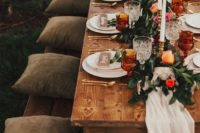 a bright fall wedding tablescape with an airy runner, bold blooms, foliage, candles and amber glasses plus gold cutlery