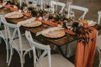 a bright fall wedding tablescape with an orange runner, greenery and candlees, gold chargers and neutral napkins is a lovely idea for the fall