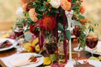 a bright floral wedding centerpiece with rust, orange, creamy blooms and greenery plus burgundy candles