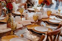 a bright modern wedding tablescape with amber napkins, glasses and vases, red and rust blooms and grasses