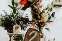 a bright rustic centerpiece of greenery and blooms, a tree branch cut with a table number for a fall tablescape