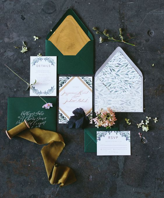 a bright wedding invitation suite with emerald envelopes and gold lining and botanical invites