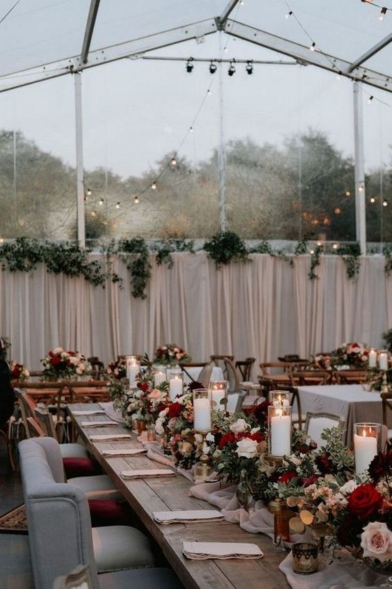 a burgundy and blush fall wedding reception with candles and chic chairs looks very cozy and inviting