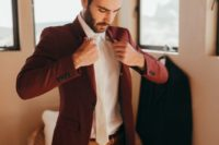 a burgundy suit, a white shirt and a white tie for a bold and statement-like fall groom's look
