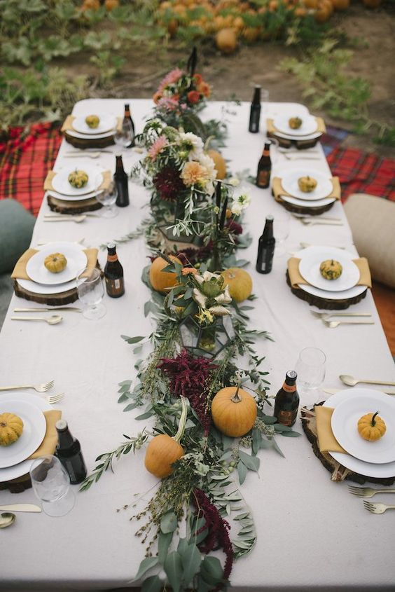 a casual outdoor fall wedding reception with greenery and burgundy blooms, pumpkins on plates and wooden slice chargers