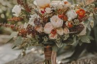 a catchy fall wedding bouquet of blush and orange flowers, berries, greenery and dark foliage plus pink ribbons is a stunning idea