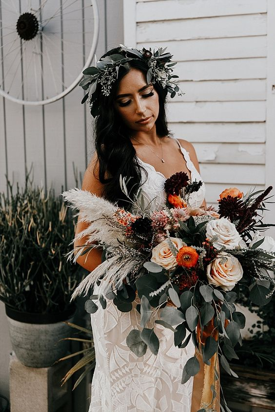 a catchy fall wedding bouquet of deep purple, neutral and rust blooms, greenery and pampas grass is an amazing textural arrangement for a fall boho bride