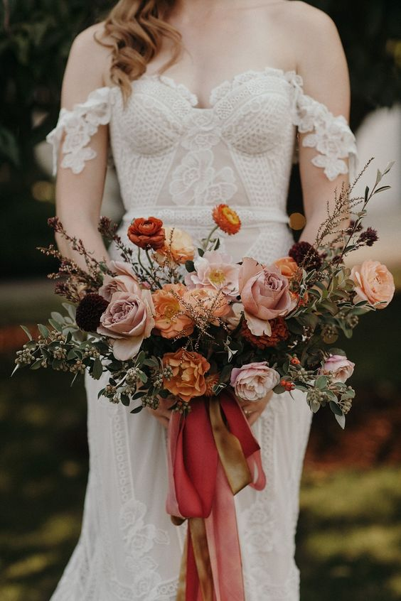 a catchy fall wedding bouquet of pale pink, rust, orange, deep purple blooms, greenery, twigs, berries is a bold and cool idea for a delicate bridal look