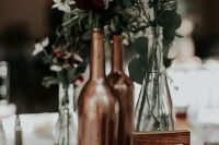 a chic and simple wedding centerpiece of copper candleholders and bottles as vases for greenery and dark and white blooms