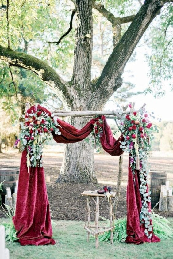 a chic fall wedding arch of burgundy velvet, greenery and burgundy blooms is very refined