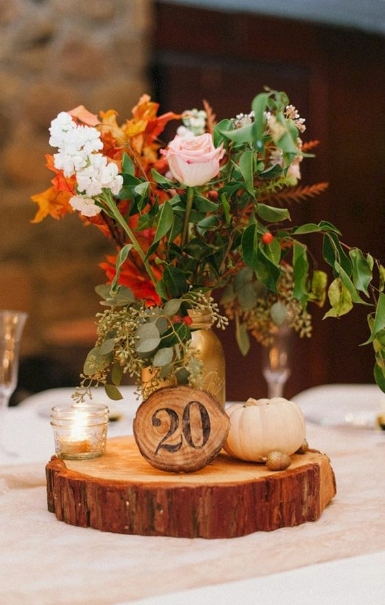 a chic fall wedding centerpiece of a wood slice, pumpkins, candles and blush and white blooms and fall foliage