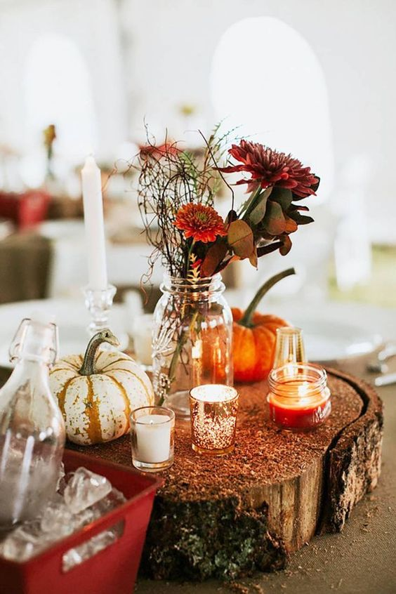 a chic fall wedding centerpiece of a wood slice, pumpkins, candles and burgundy flowers and greenery
