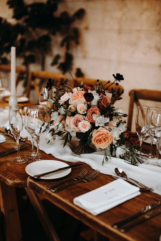 a chic fall wedding tablescape with neutral linens, a bright and white floral centerpiece, tall candles and elegant cutlery is amazing