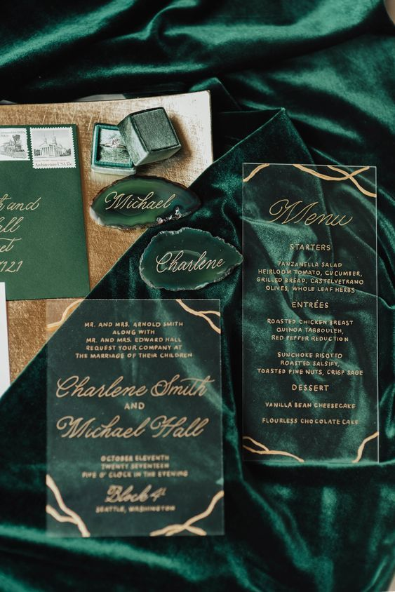 a chic invitation suite of acryl with gold touches and an emerald green envelope plus agates
