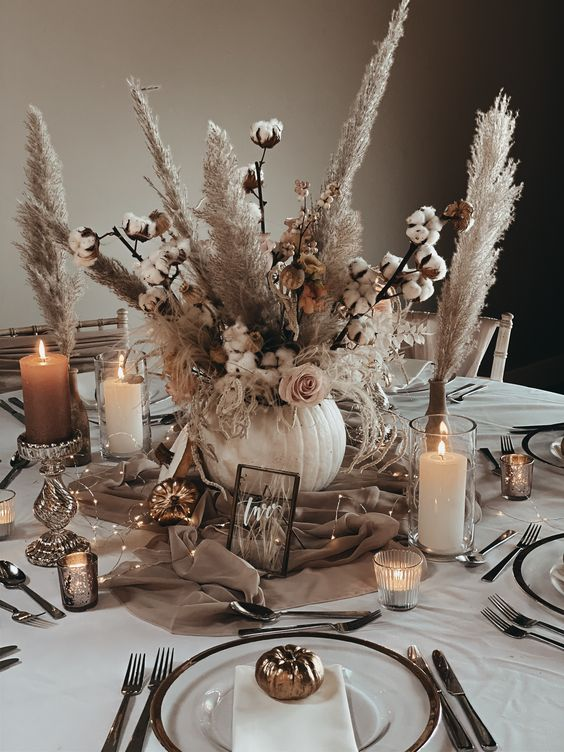 a chic neutral fall wedding tablescape with a pumpkin vase with cotton and pampas grass, candles, a taupe runner with LED lights, neutral linens