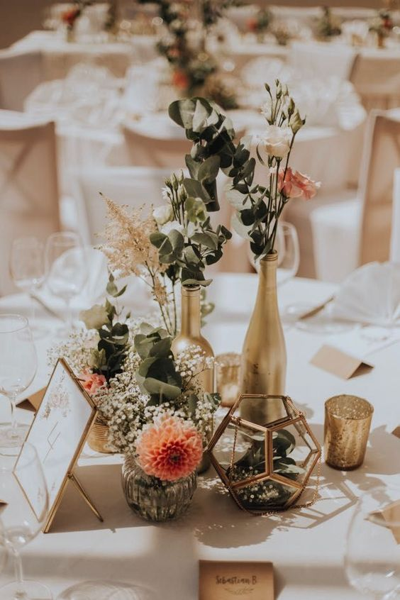 a cluster fall wedding centerpiece of gilded bottles and candleholders, greenery, white and pink roses, candles and baby's breath