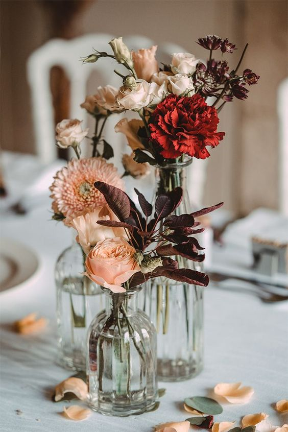 a cluster wedding centerpiece of vases with dark foliage, blush and red blooms is very lovely for fall