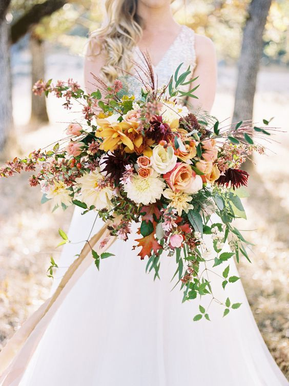 a colorful and dimensional fall bouquet with yellow, pink, white, red flowers and greenery and red leaves plus a cascade for a catchier look