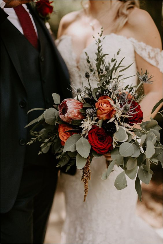a colorful fall wedding bouquet of orange, deep red and purple blooms, a pink king protea, greenery and thistles is gorgeous