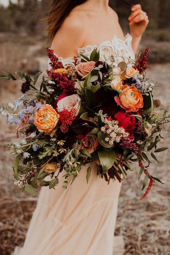 a colorful fall wedding bouquet of orange, pink, red, blue, lilac blooms, foliage and greenery is a catchy fall wedding solution