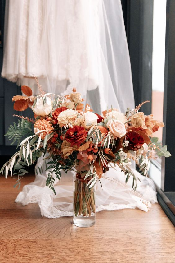 a colorful fall wedding bouquet of white, blush, rust, orange, deep red blooms, greenery, berries and bright fall leaves will match many bridal styles