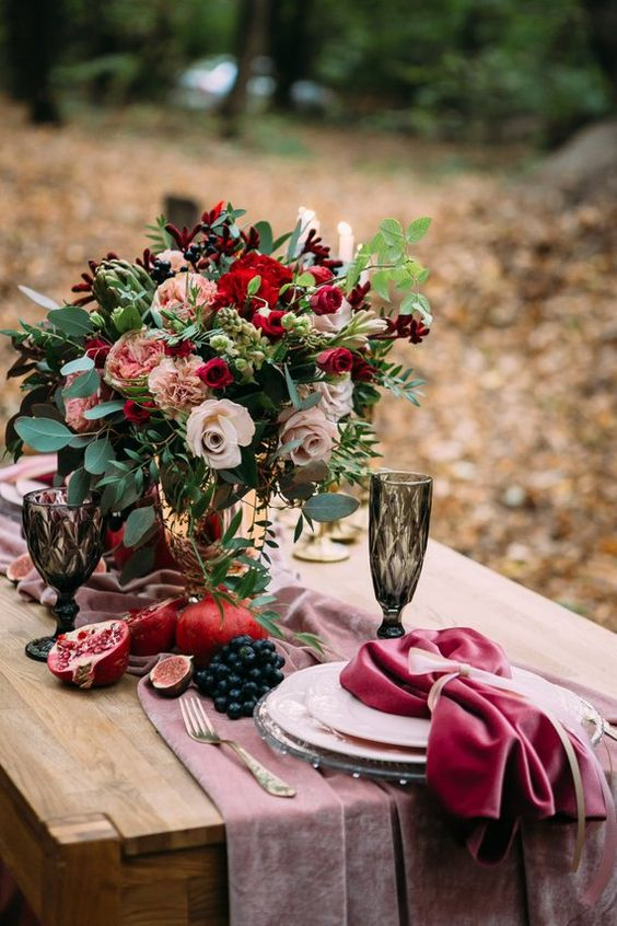 a colorful fall wedding centerpiece of greenery, blush, pink and red blooms and berries and fruits on the table