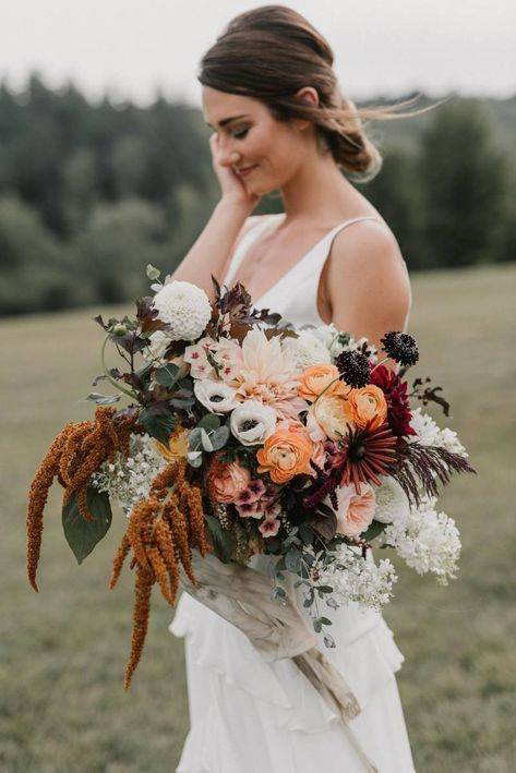 a contrasting fall wedding bouquet of orange, white, pink, burgundy, deep red and deep purple blooms, greenery and bold foliage and some cascading touches