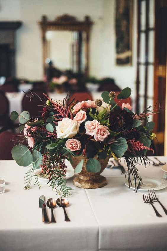 a contrasting fall wedding centerpiece of white, light pink and purple blooms and greenery and berries