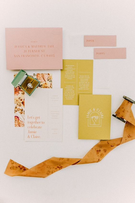a cool fall wedding invitation suite in pink, mustard and with a floral printed envelope plus an orange floral ribbon