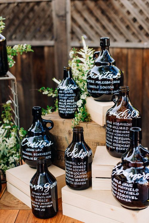 a cool wedding seating chart of oversized wine bottles and greenery is perfect for a vineyard wedding, not only a fall one