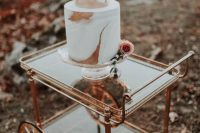 a copper cart and a white and copper marbled wedding cake with a pink rose is a stylish piece