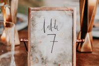 a copper frame with a table number and marble printing is a cool and bold idea for a fall wedding
