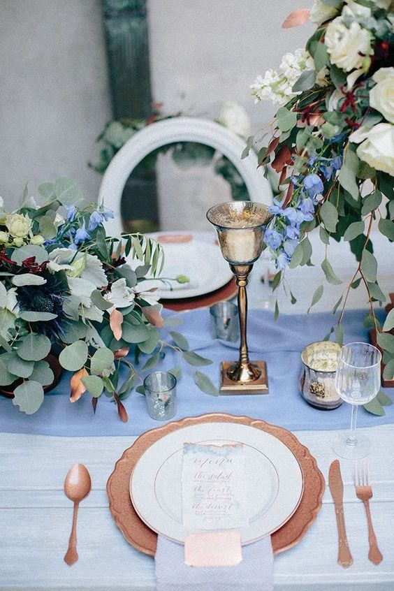 a copper placemat and cutlery, a gold candlehoder and white and blue blooms and greenery