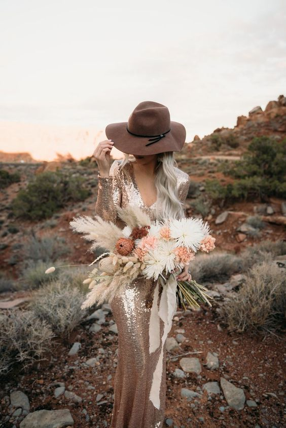a copper sequin sheath wedding dress with a V neckline and long sleeves plus a hat for a boho look