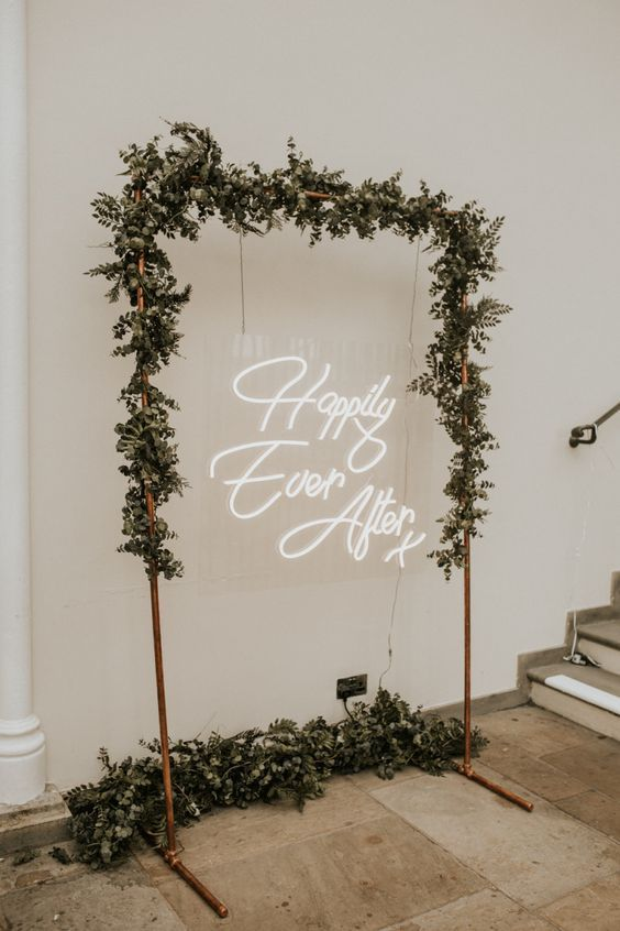a copper wedding arch with greenery and a neon light is a lovely decoration for a modern wedding