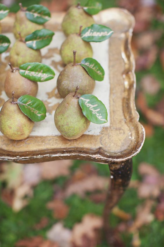 a creative fall wedding escort card display with leaves as cards - these pears can double as favors