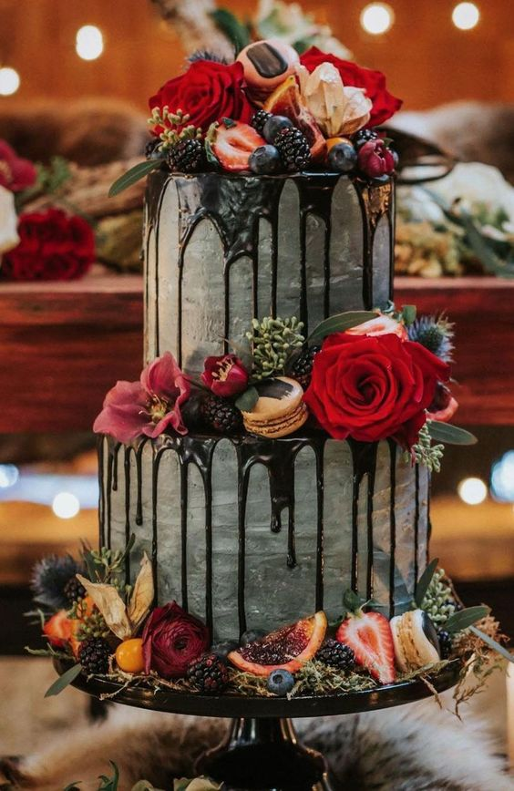 a decadent fall wedding cake in grey, with chocolate drizzle, bright blooms, citrus, berries and greenery