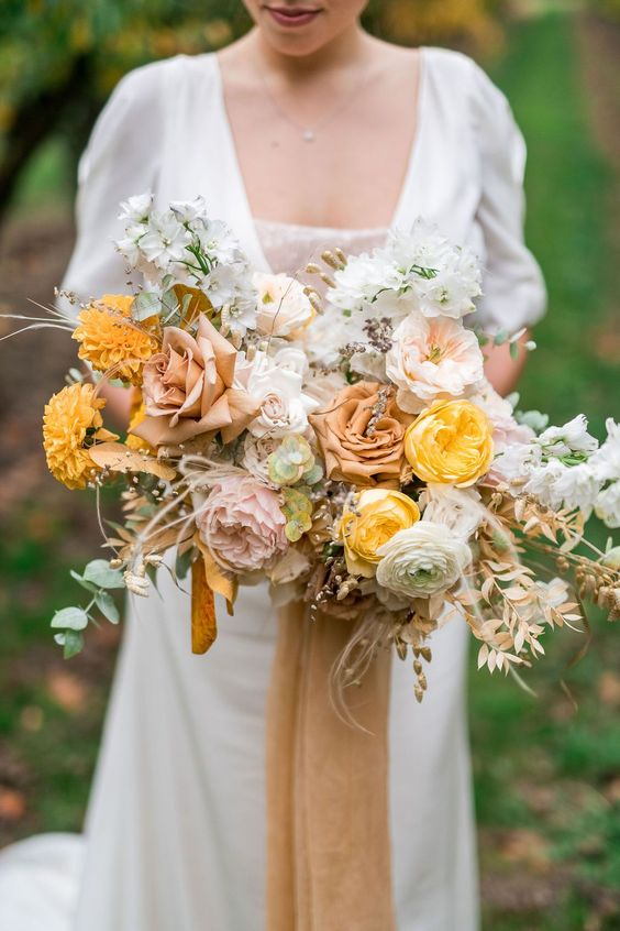 a delicate and pretty fall wedding bouquet of yellow, blush, rust blooms, greenery and dried foliage for a subtle fall bridal look