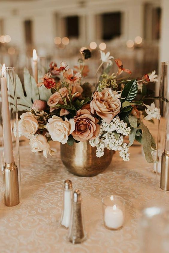 a delicate fall wedding centerpiece of a brass vase with neutral and rust-colored blooms and foliage
